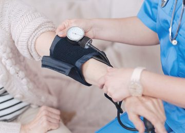 Close up of female doctor checking pressure of elderly patient